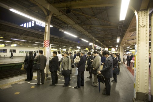 A line of Japanese business men waiting for (probably the last) train home